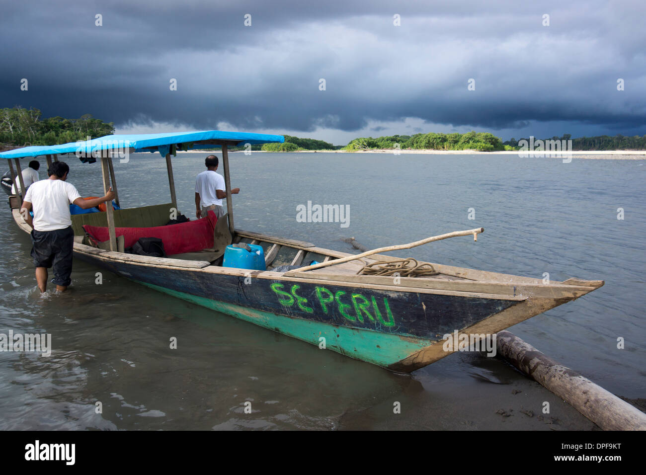 Dark clouds and tourist boat on the Manu river, Manu National Park, UNESCO World Heritage Site, Peru, South America - Stock Image