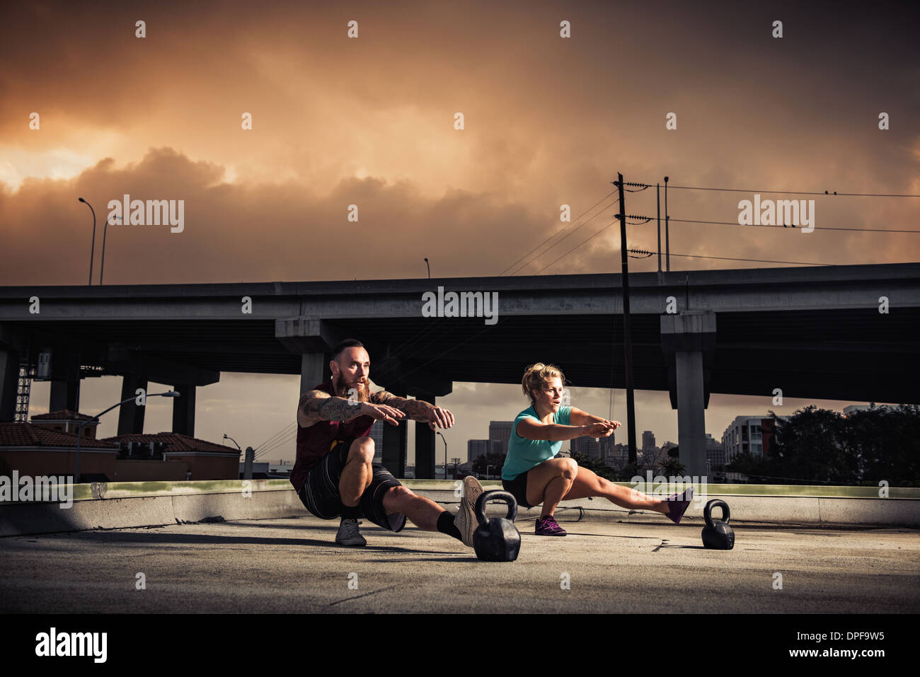 Man and woman training on gymnasium rooftop - Stock Image