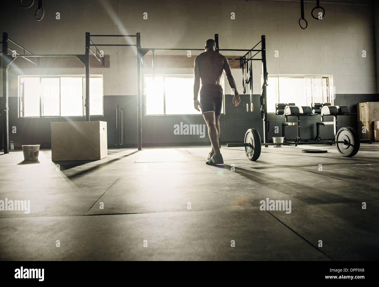 Young man preparing for exercise bar in gymnasium - Stock Image