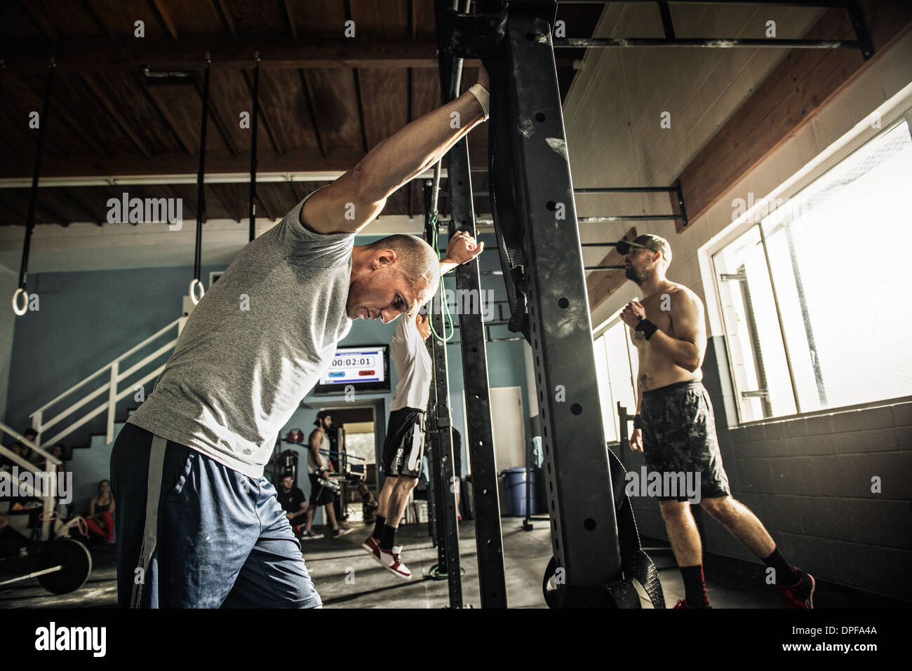Men training on exercise bar in gymnasium - Stock Image