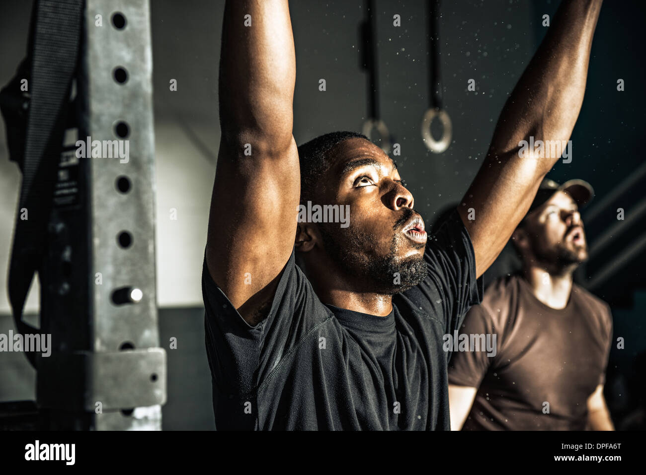 Close up of young man training on exercise bar in gymnasium - Stock Image