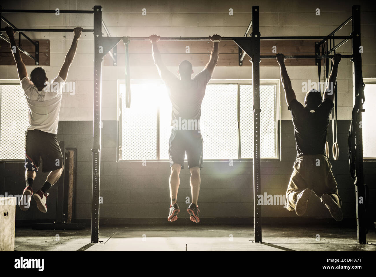 Three men doing pull ups on exercise bar in gymnasium - Stock Image