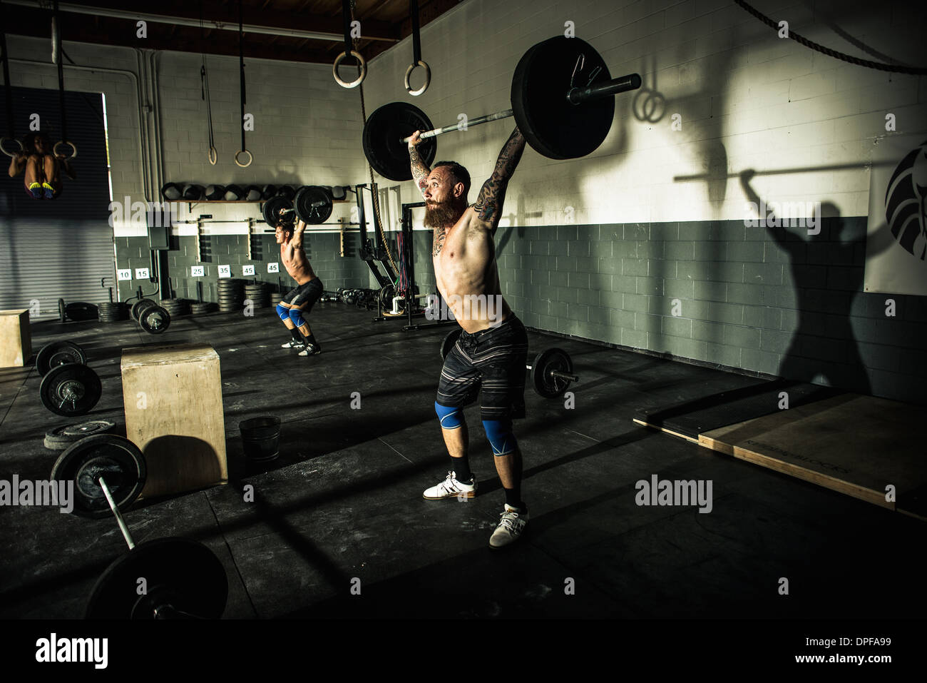 Two men lifting barbels in gymnasium - Stock Image