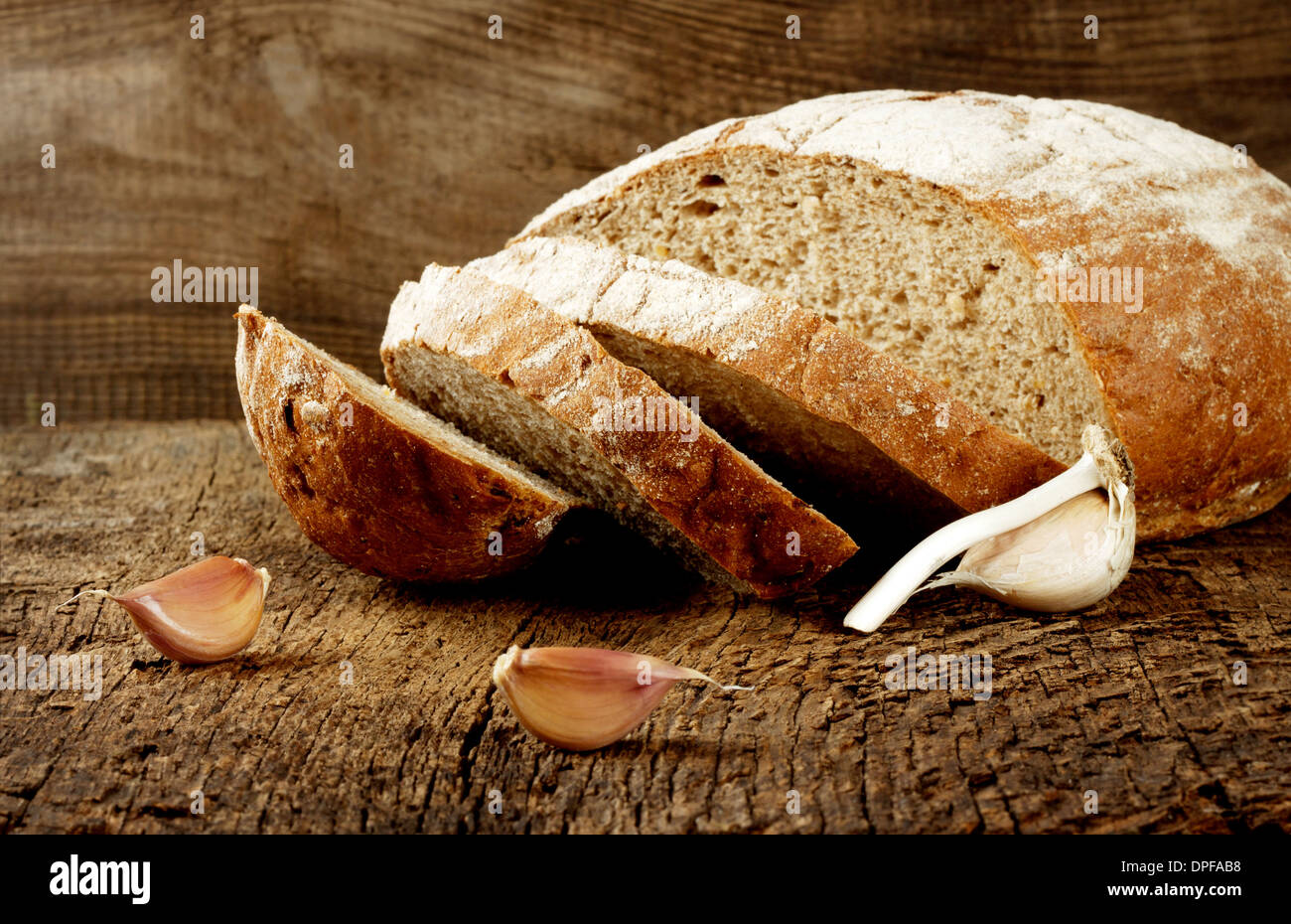 Black bread with garlic on a wooden background - Stock Image