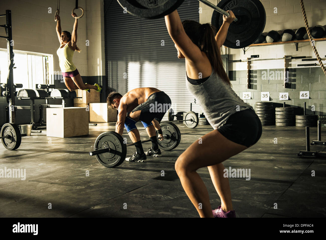 People training with barbells and gymnasium rings Stock Photo