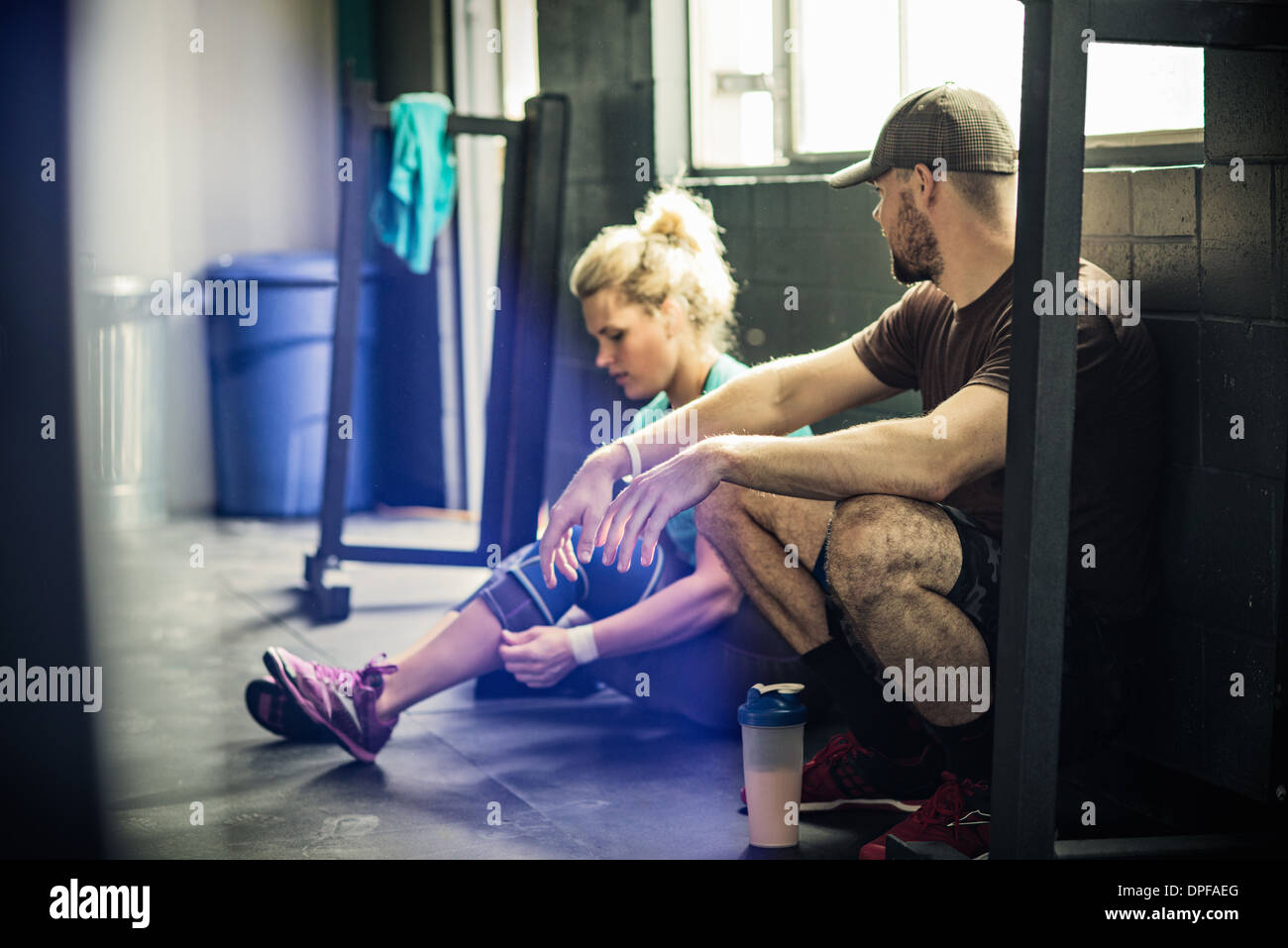 Trainer talking to young woman in gymnasium Stock Photo