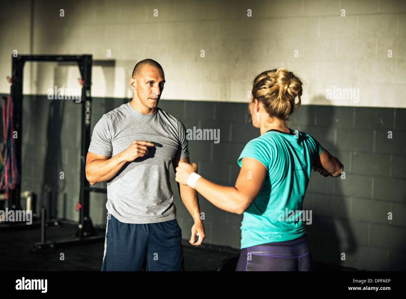 Trainer mentoring young woman in gymnasium - Stock Image