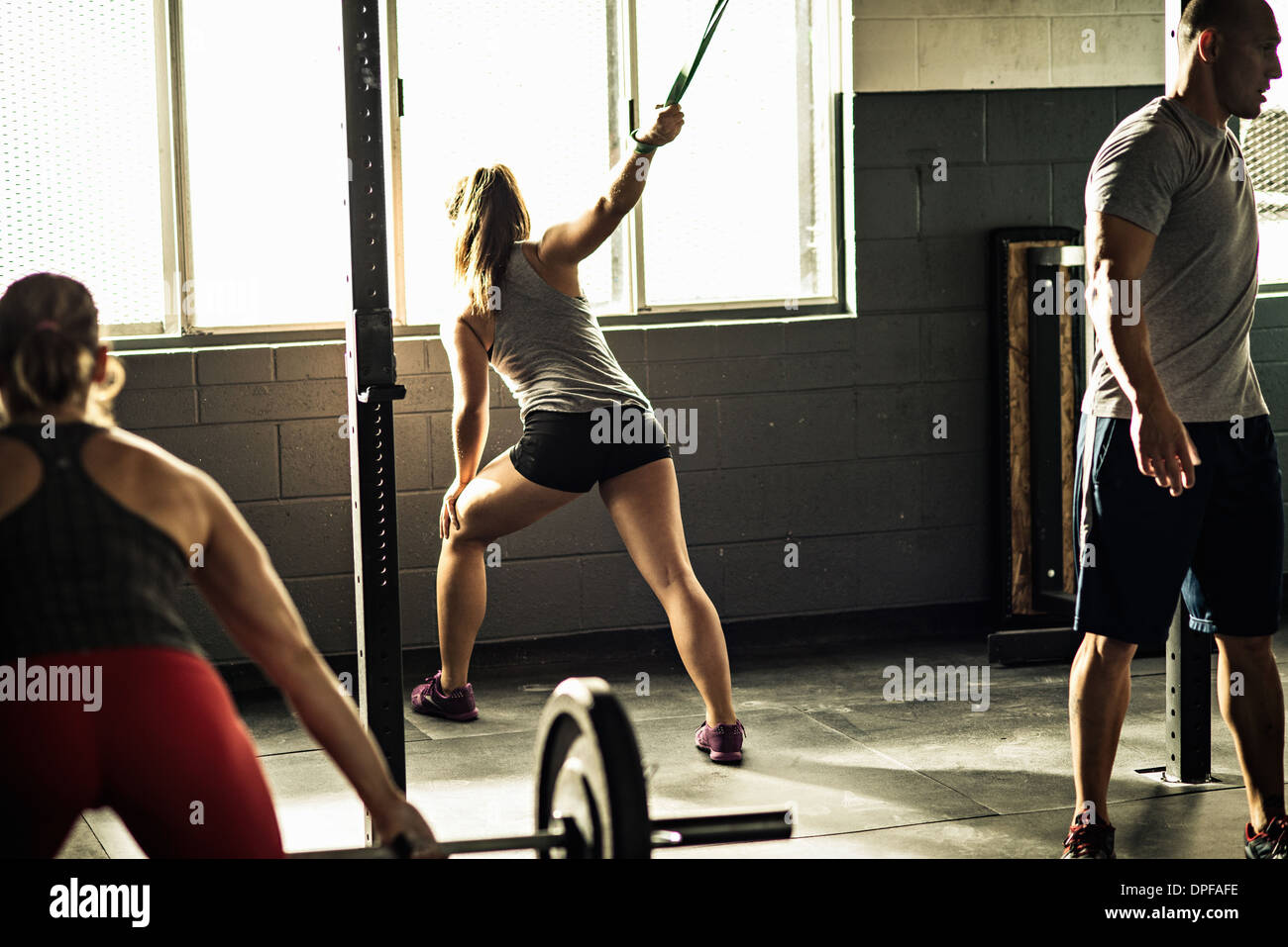 Women and trainer working out in gymnasium - Stock Image