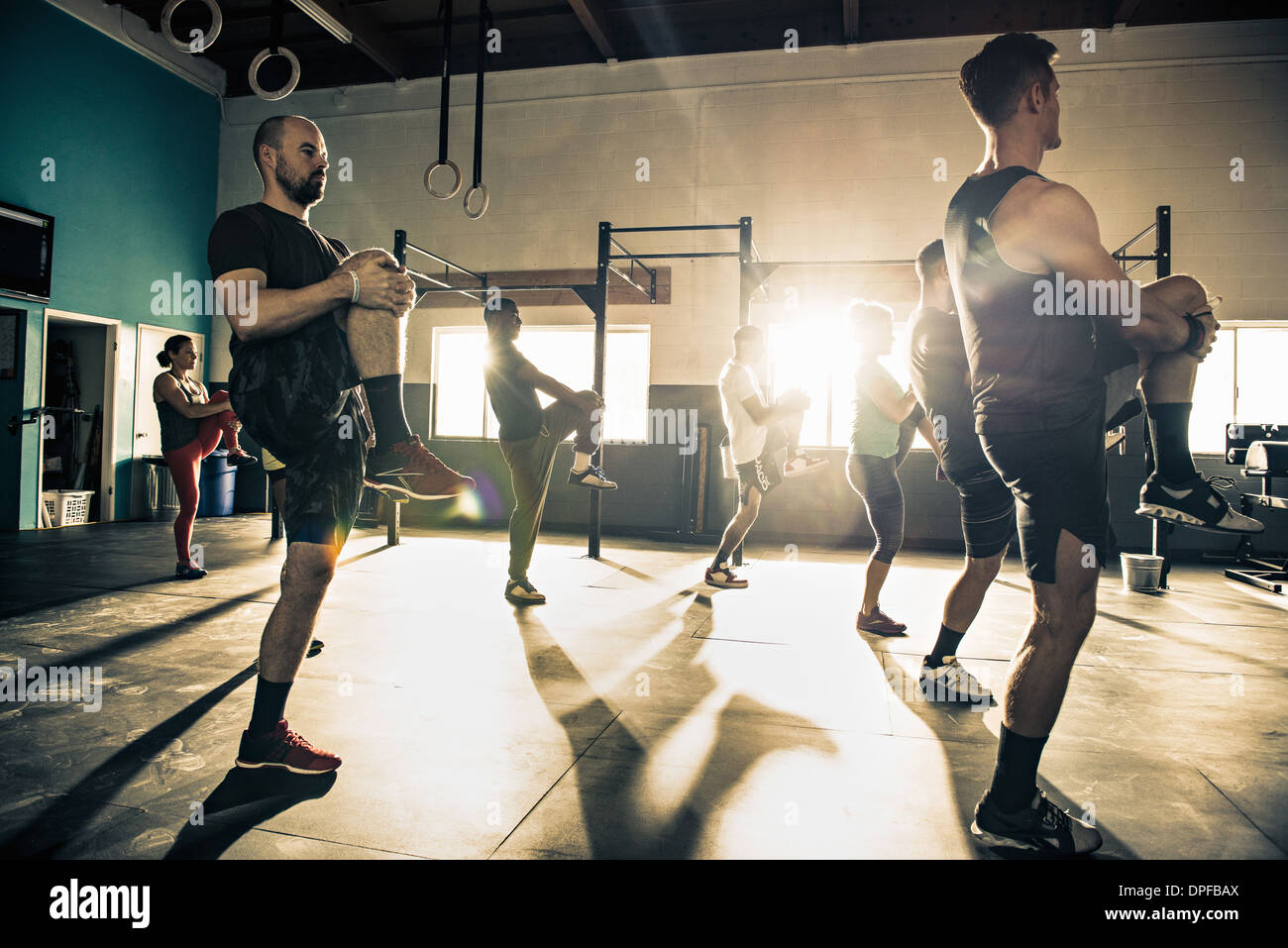 Fitness group training together in gymnasium - Stock Image