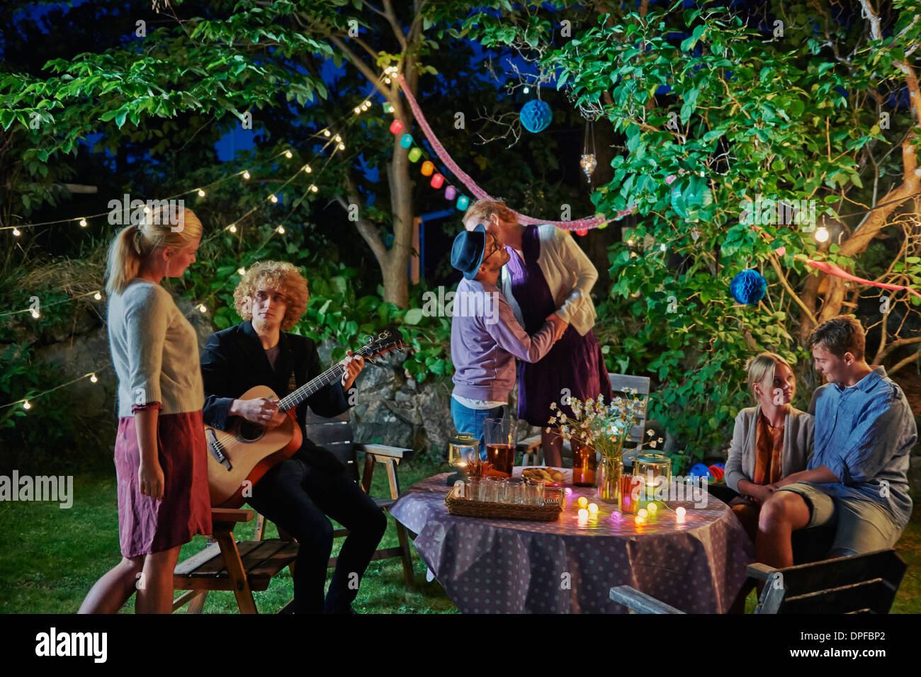 Three couples enjoying evening garden party - Stock Image
