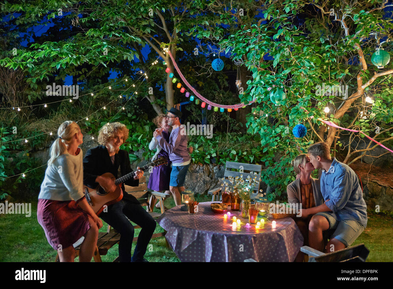 Three couples having fun at garden party at night - Stock Image