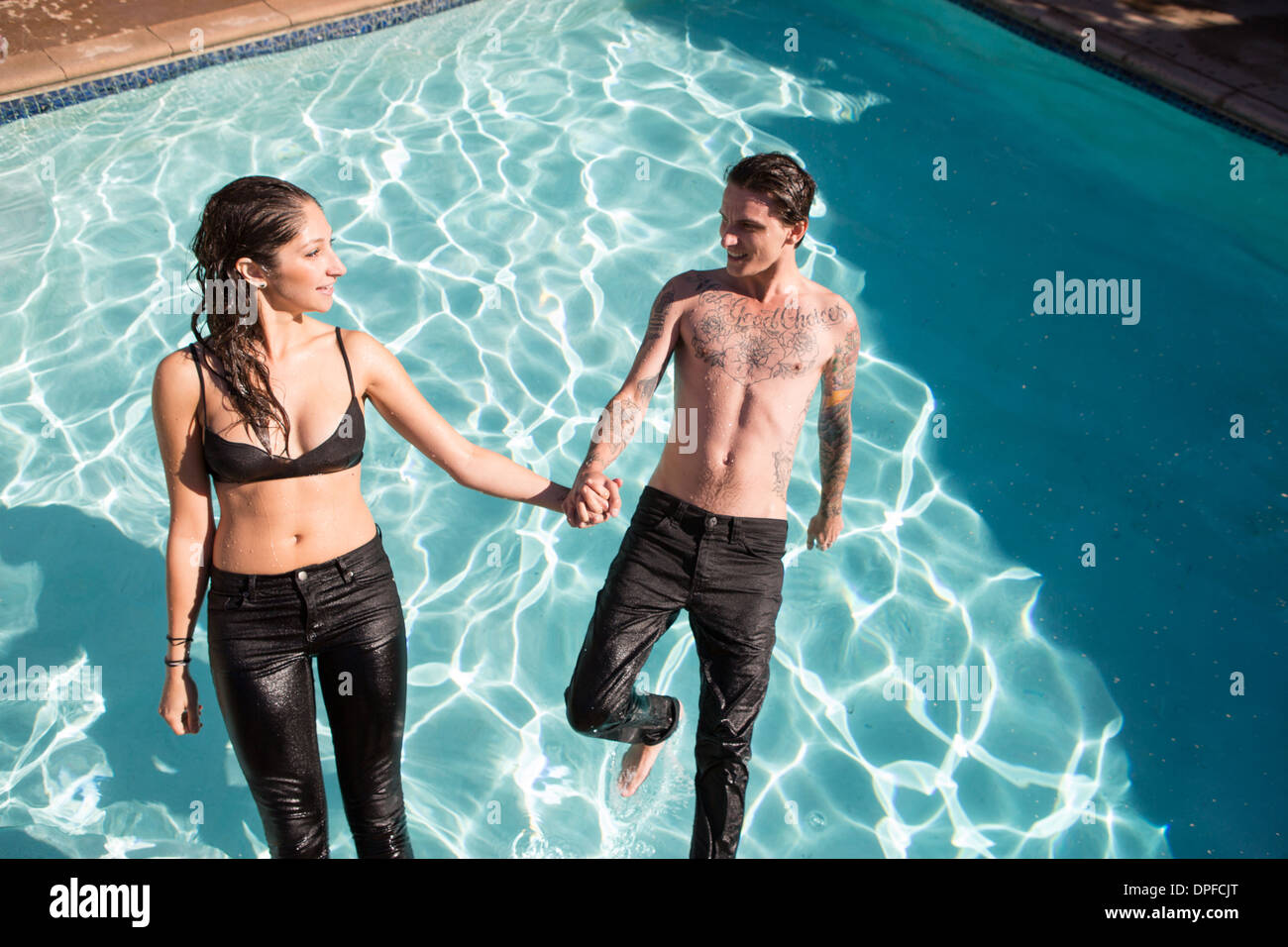 Young couple falling backwards into swimming pool - Stock Image