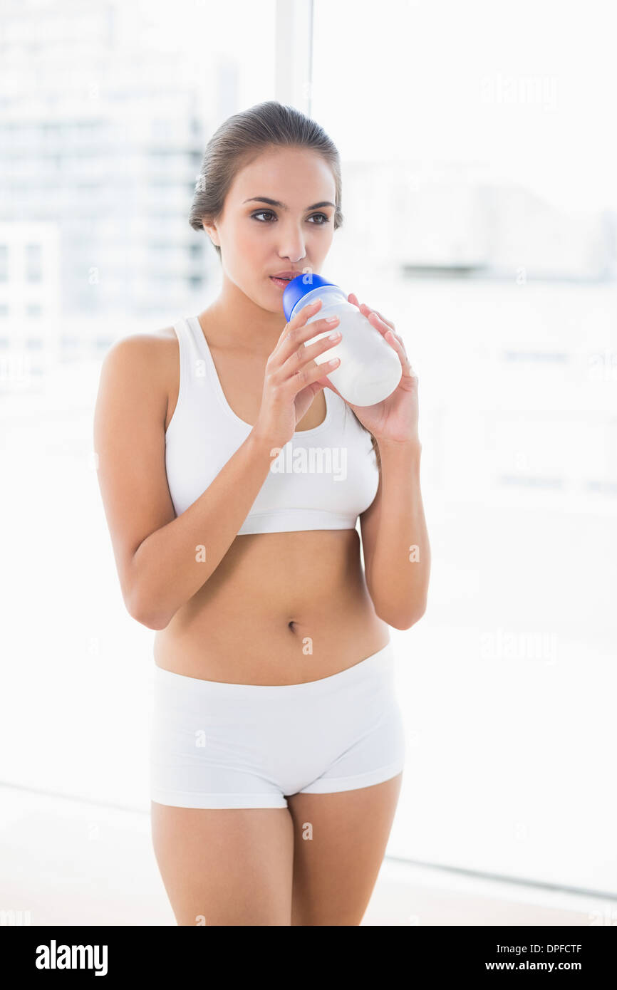 Peaceful sporty brunette drinking from a water bottle - Stock Image