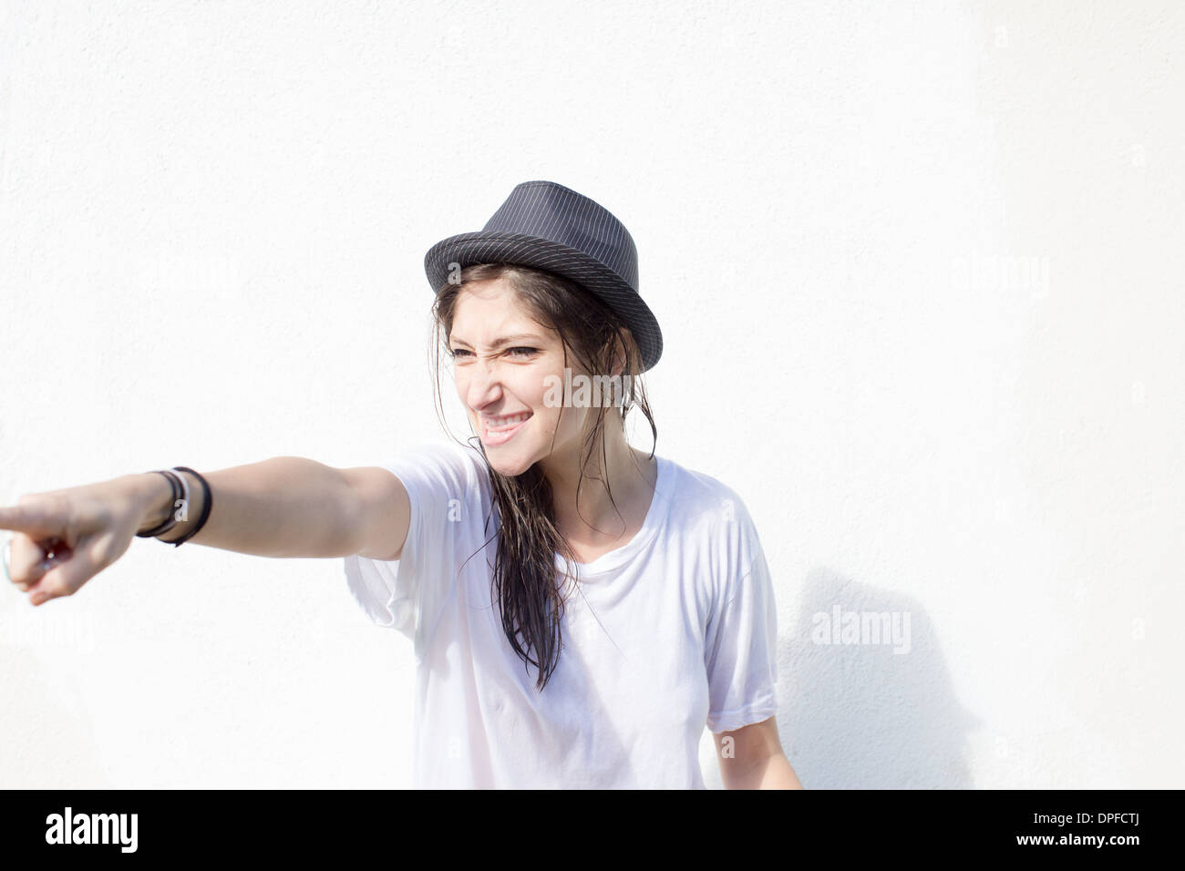 Young woman with attitude pointing finger - Stock Image