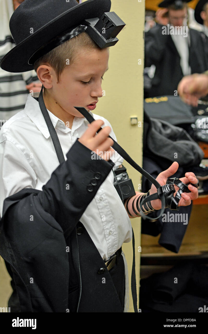 Young religious Jewish boy puts on phylacteries - teffilin - at the Lubavitch synagogue in Crown Heights, Brooklyn, New York - Stock Image