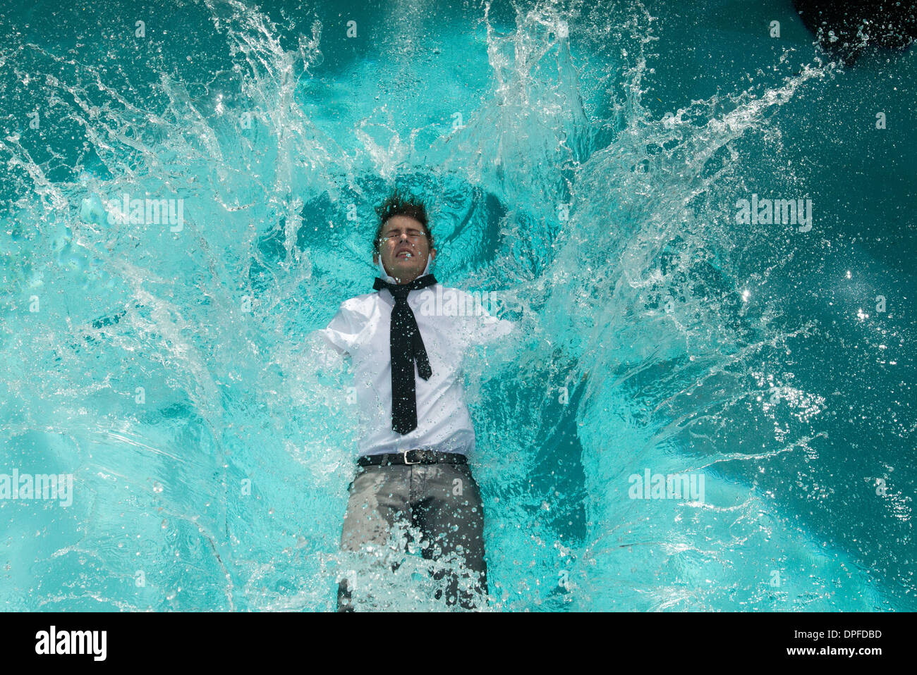 Young man in clothes falling into swimming pool - Stock Image