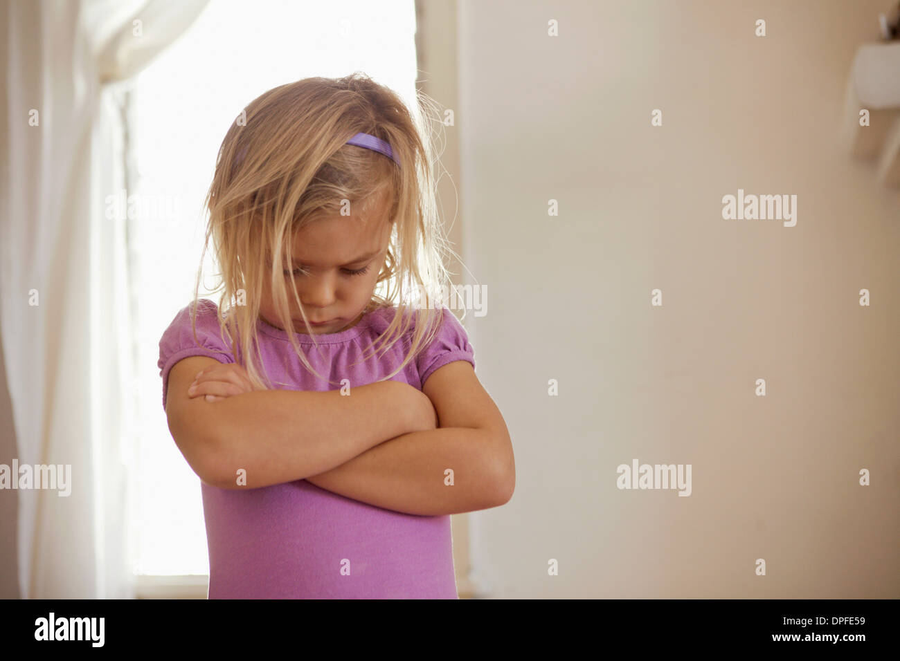 Young girl with head down and arms folded having tantrum - Stock Image