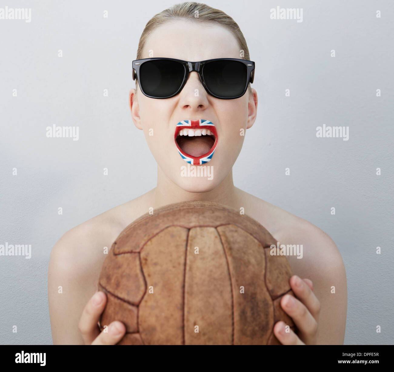 Woman with British flag lipstick, holding soccer ball - Stock Image