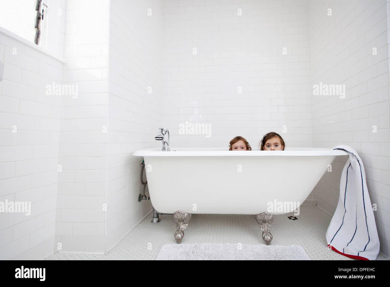 Portrait of two young girls peeking over bath - Stock Image
