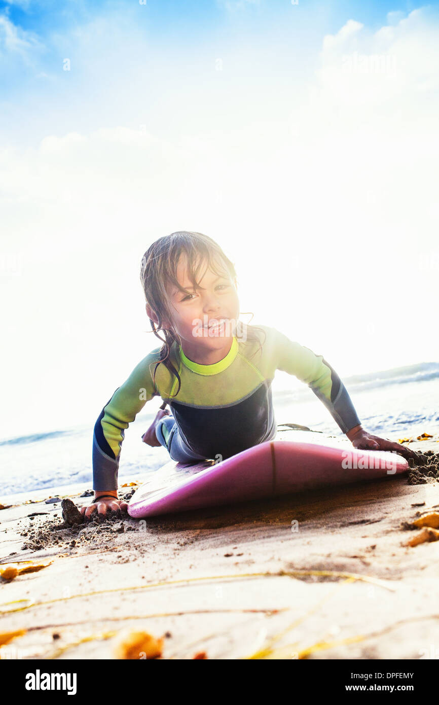 Young girl practicing surfing on beach, Encinitas, California, USA - Stock Image