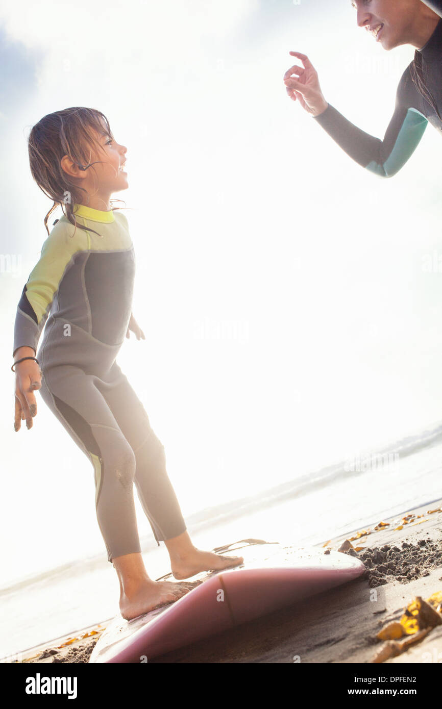 Mother and daughter practicing surfing on beach, Encinitas, California, USA - Stock Image