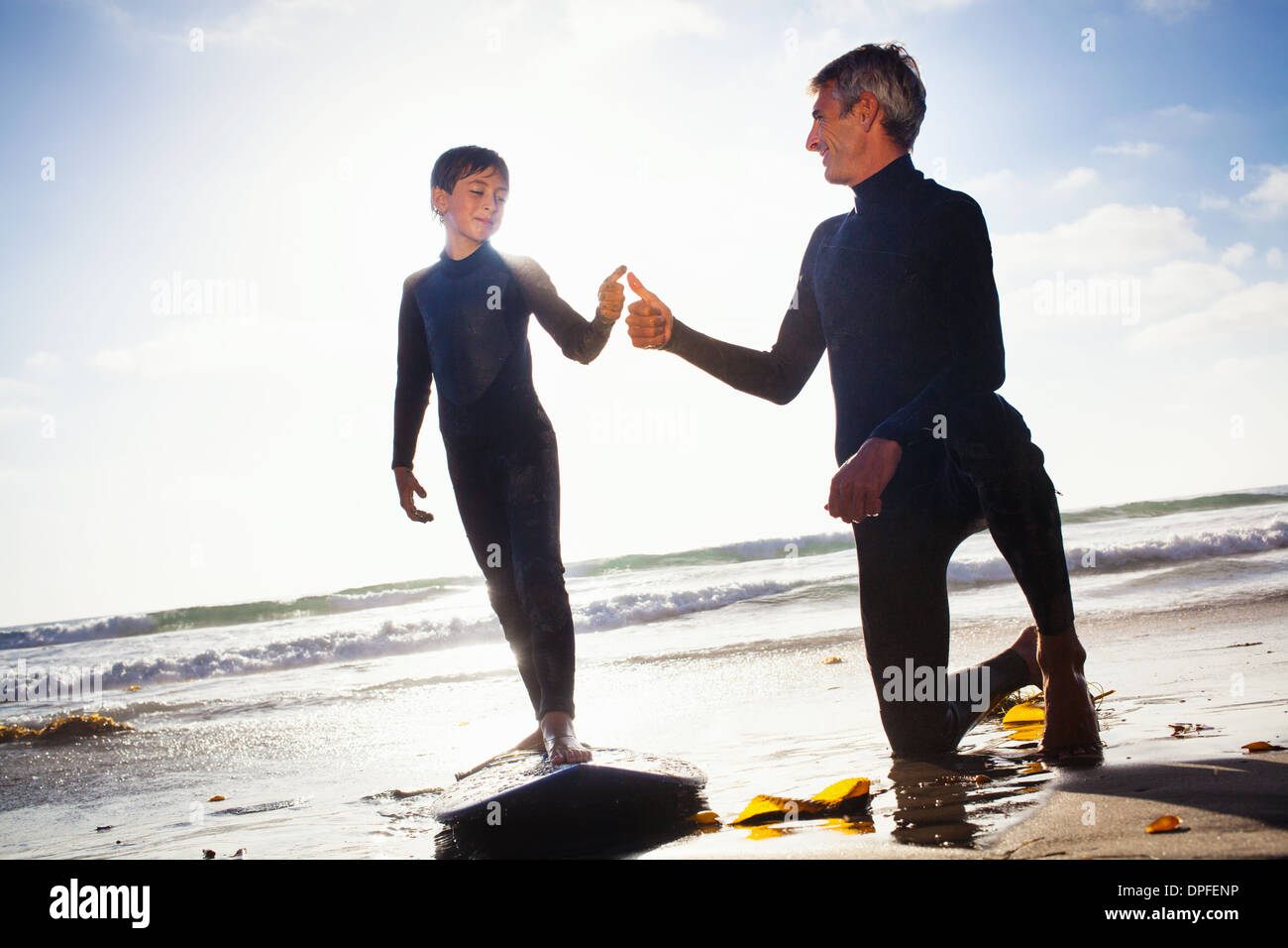 Father and son with surfboard on beach, Encinitas, California, USA - Stock Image
