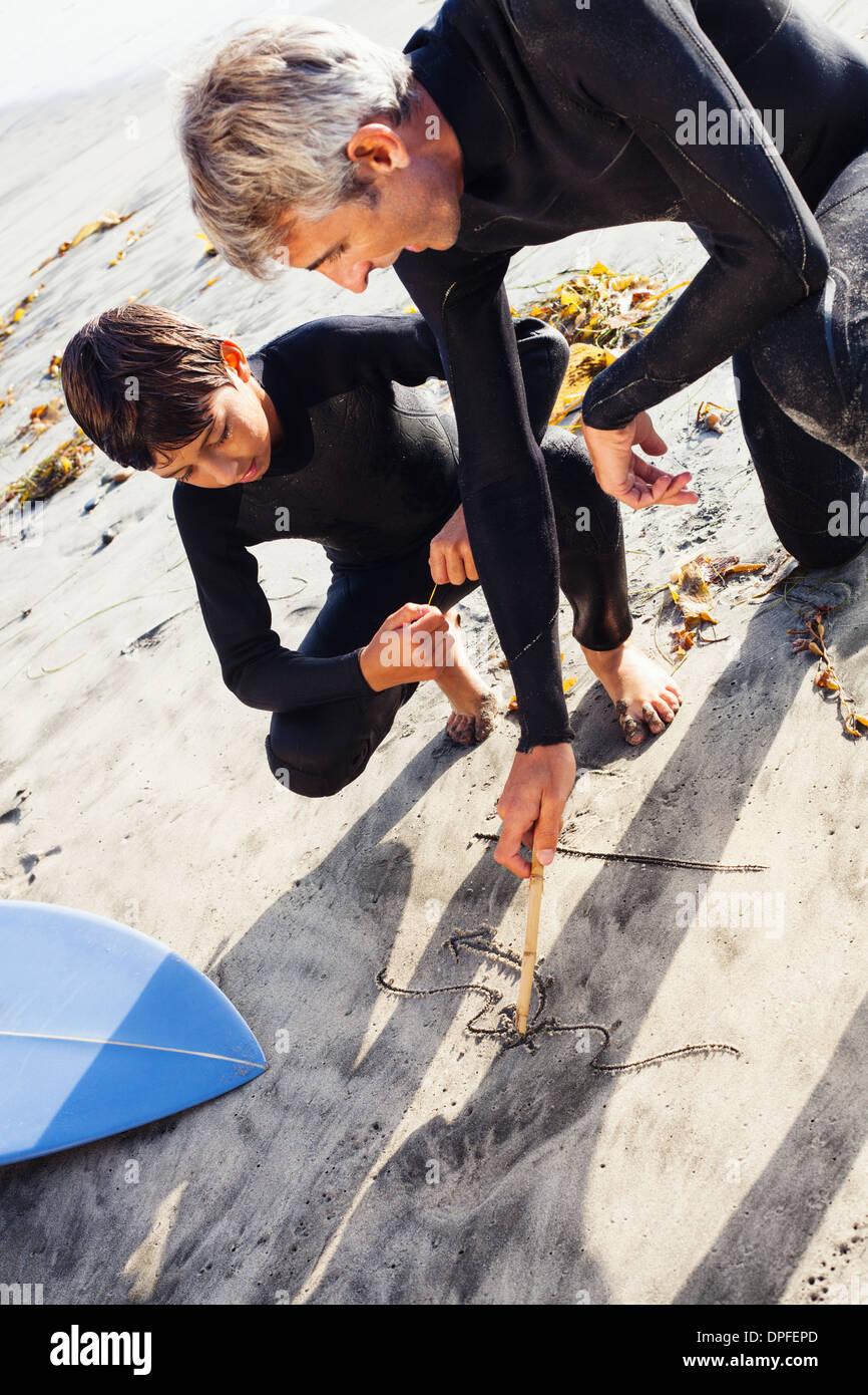 Father and son surfers at beach, Encinitas, California, USA - Stock Image