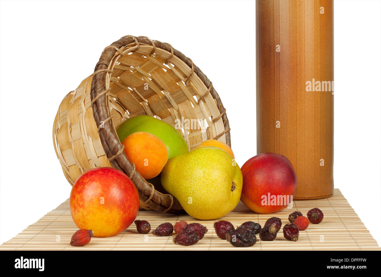 Fruit spill out of the basket on a bed of straw isolated on white background - Stock Image