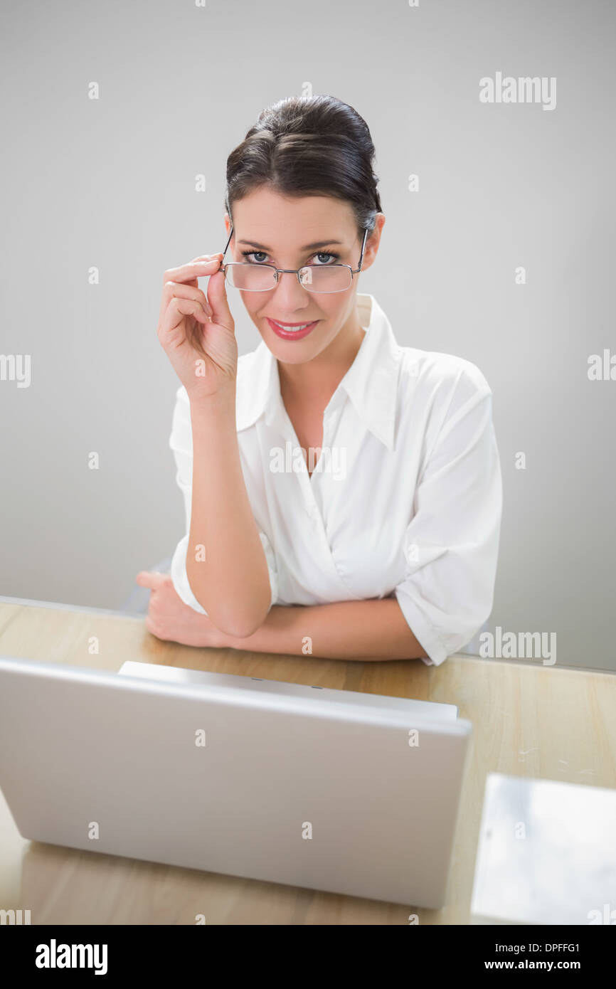 Smiling businesswoman with classy glasses posing - Stock Image