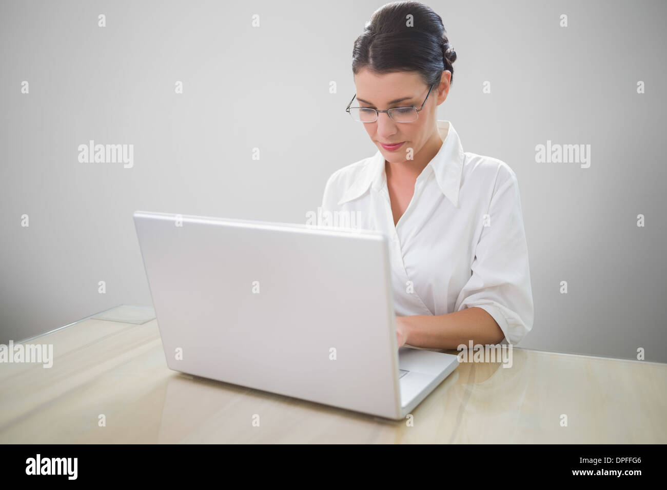 Focused businesswoman with classy glasses posing - Stock Image