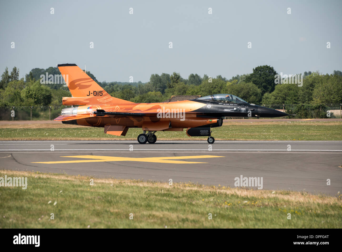 Lockheed Martin F-16 fighter jet of the Royal Netherlands Air Force demonstration team in it's striking orange at RIAT - Stock Image