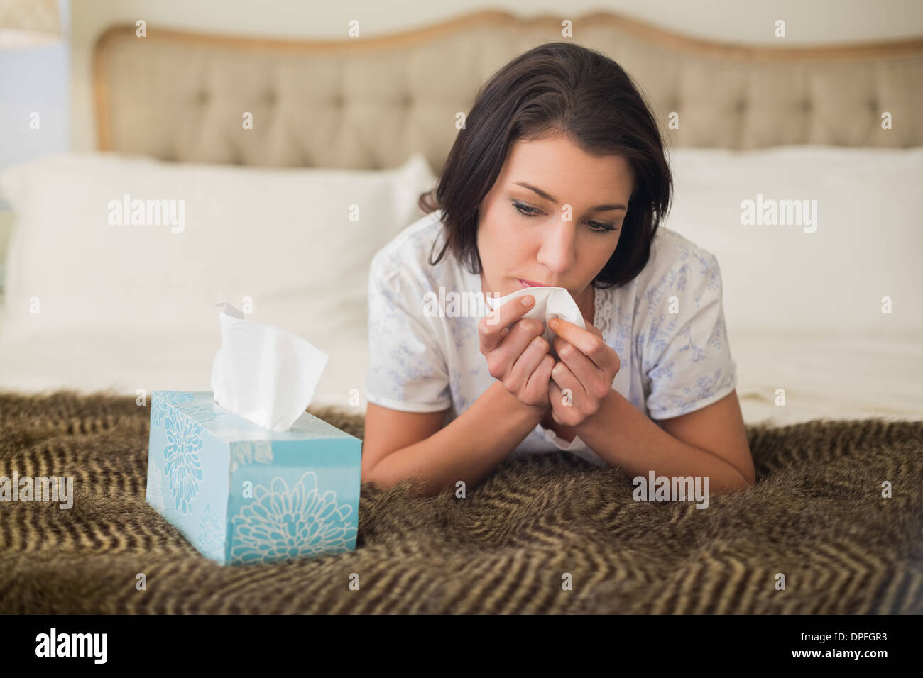 Troubled pretty brown haired woman crying on her bed - Stock Image