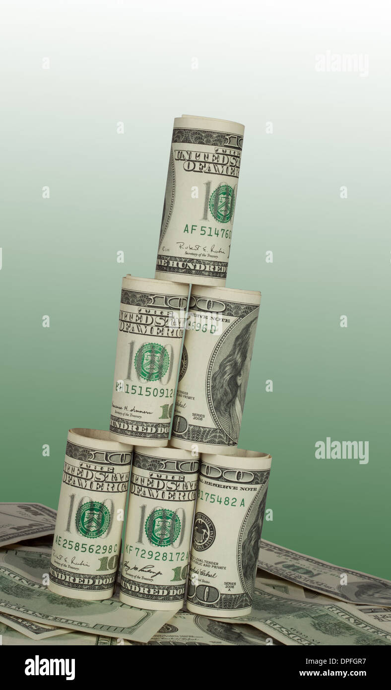 Leaning Tower of hundred dollar bills on green background - Stock Image