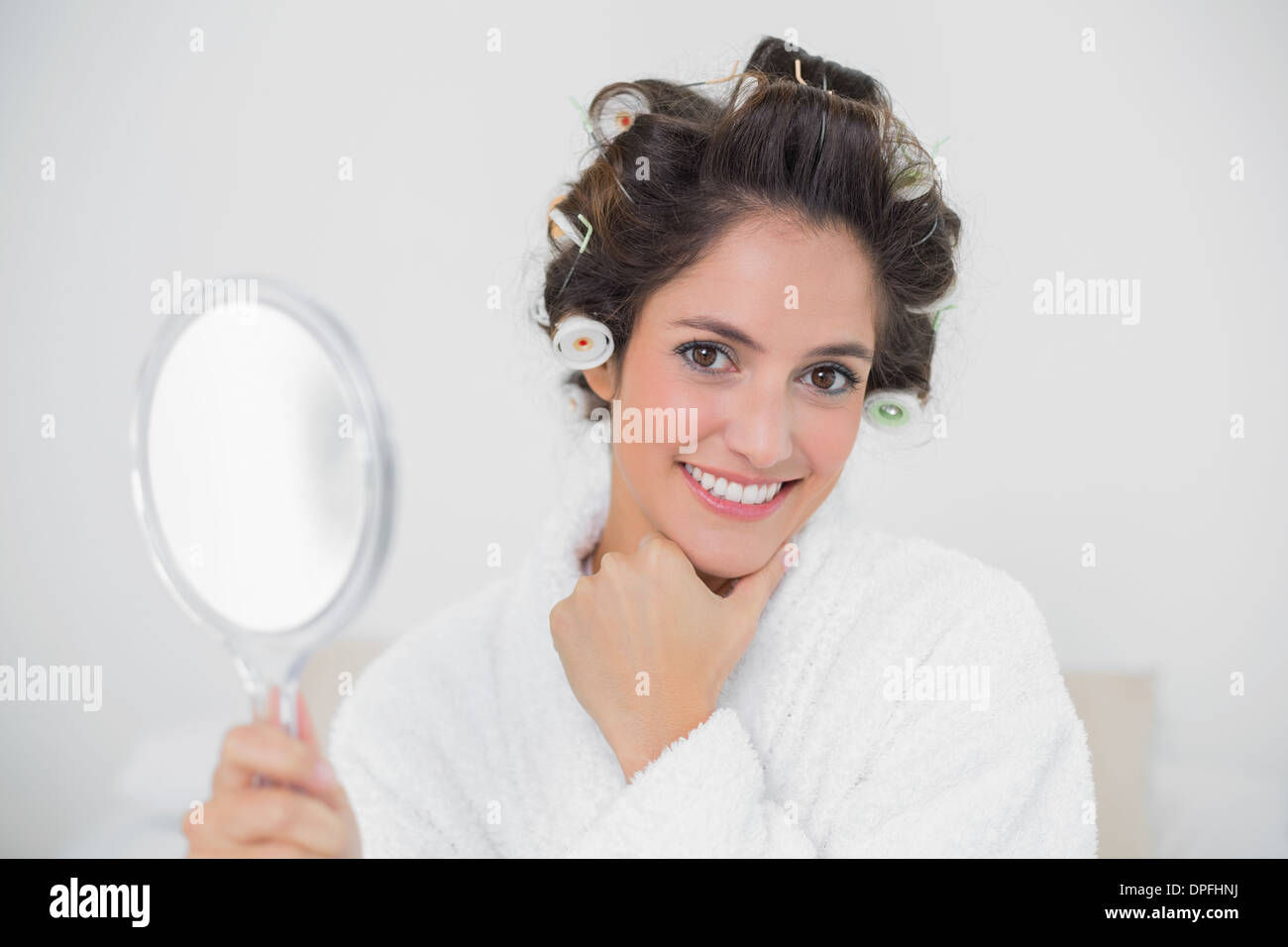 Gleeful natural brunette holding hand mirror - Stock Image