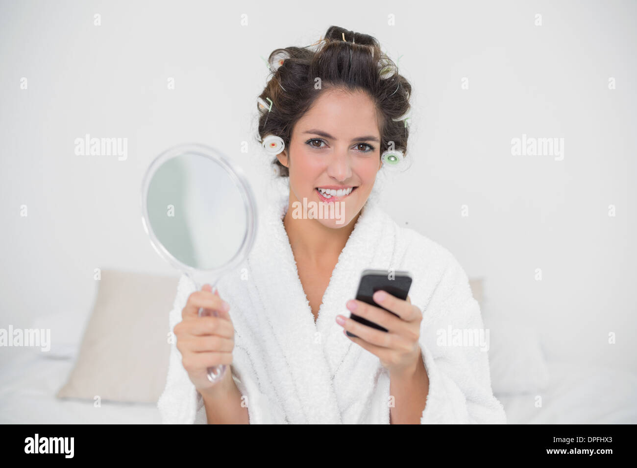 Unsure natural brunette holding mirror and smartphone - Stock Image