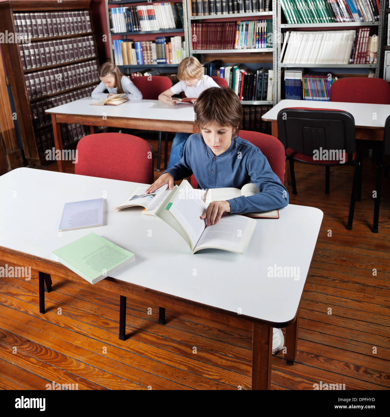 Little Boy Reading Books In Library - Stock Image