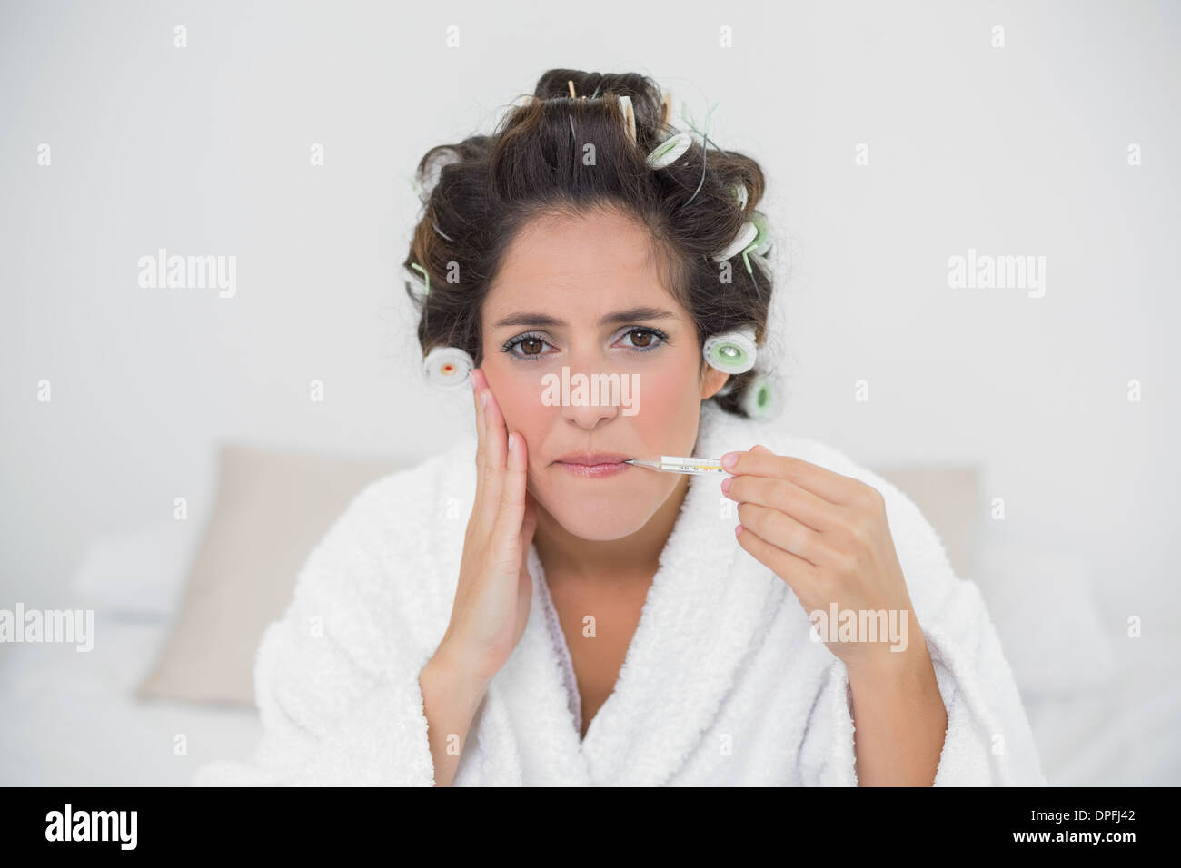 Grimacing natural brunette holding thermometer - Stock Image