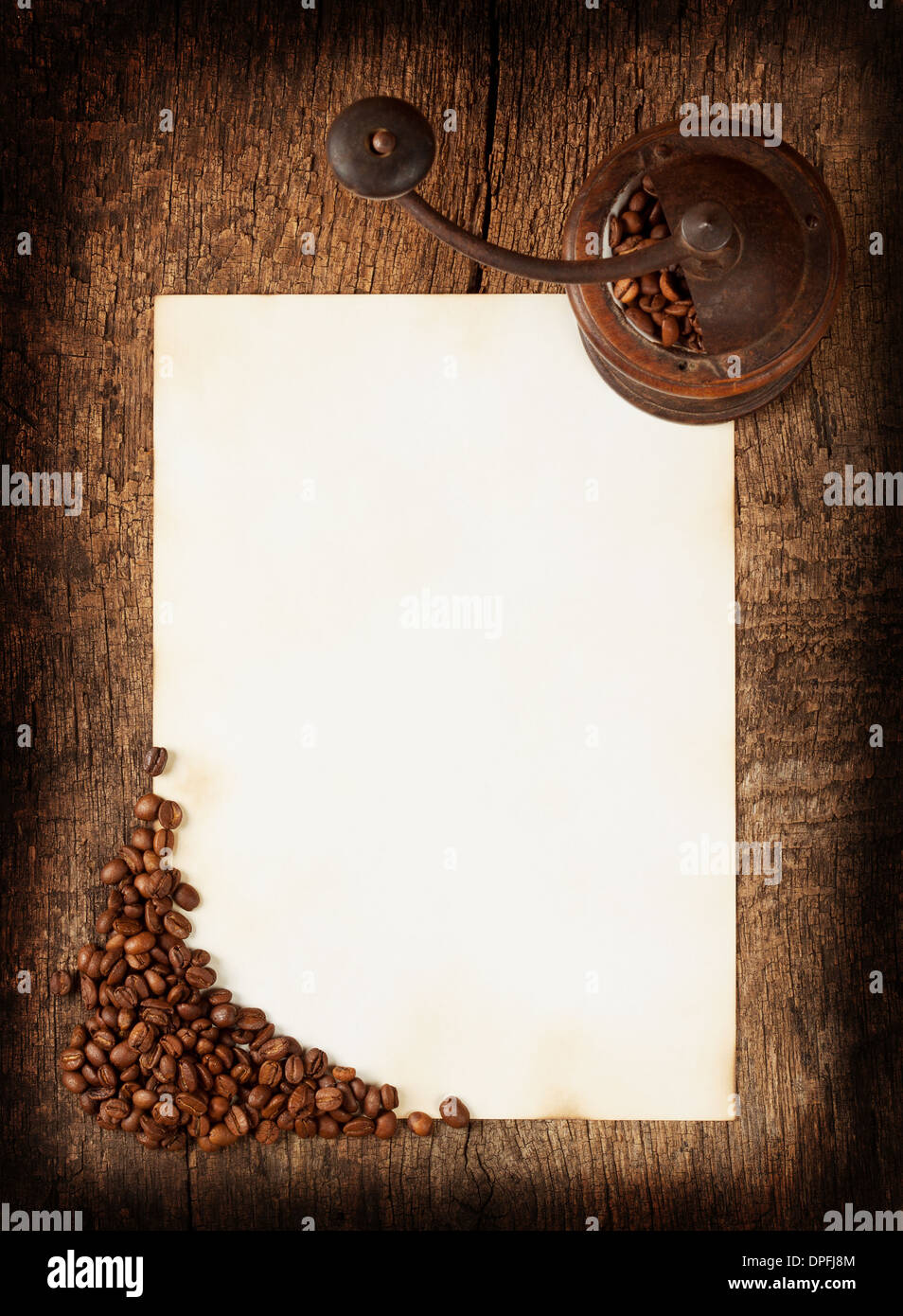 Old burnt sheet with a coffee grinder and coffee beans - Stock Image