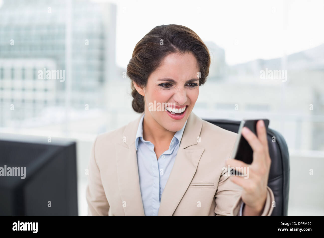 Furious businesswoman shouting at smartphone - Stock Image