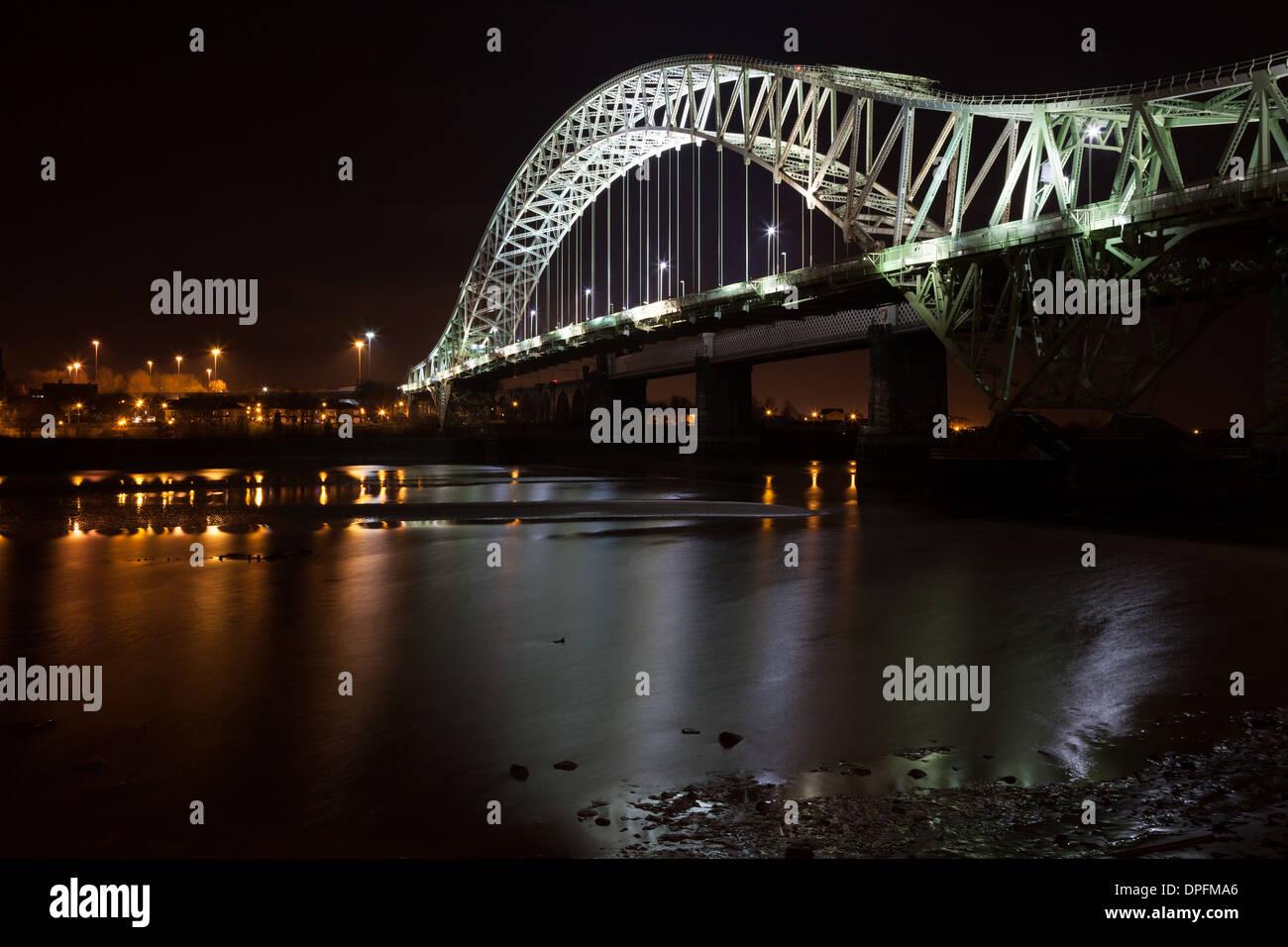 The Silver Jubilee Bridge, also known as the Runcorn Bridge in Cheshire illuminated at night. - Stock Image