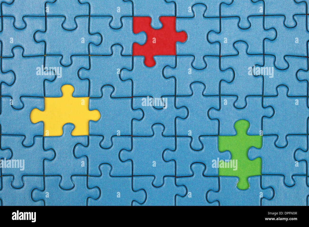 Jigsaw Puzzle with missing pieces in three different colors - Stock Image