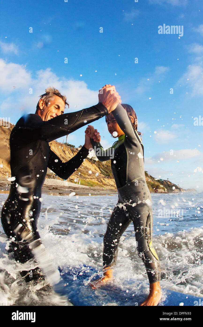 Father and daughter jumping in sea, Encinitas, California, USA - Stock Image
