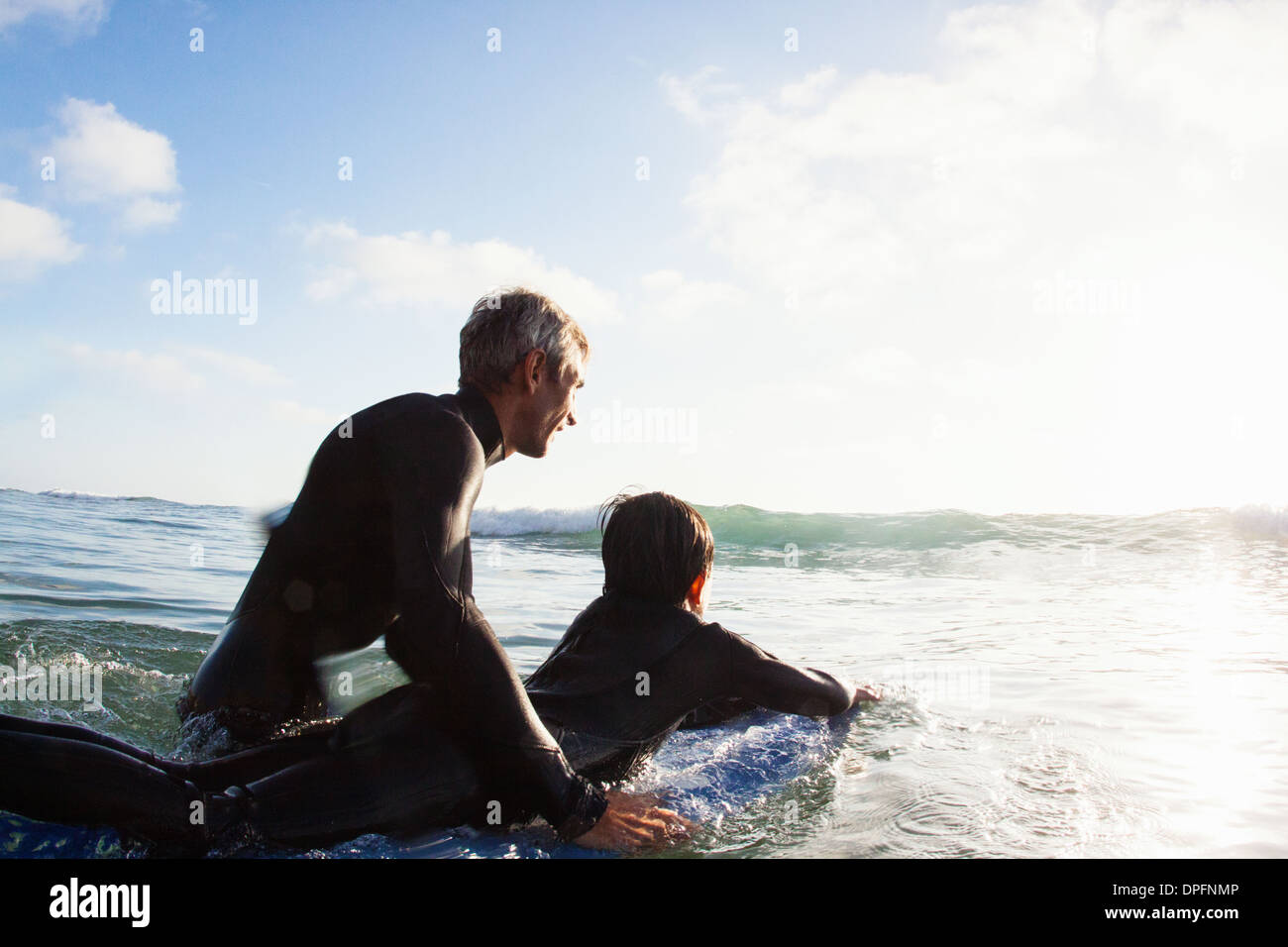 Father and son at sea with surfboard, Encinitas, California, USA - Stock Image