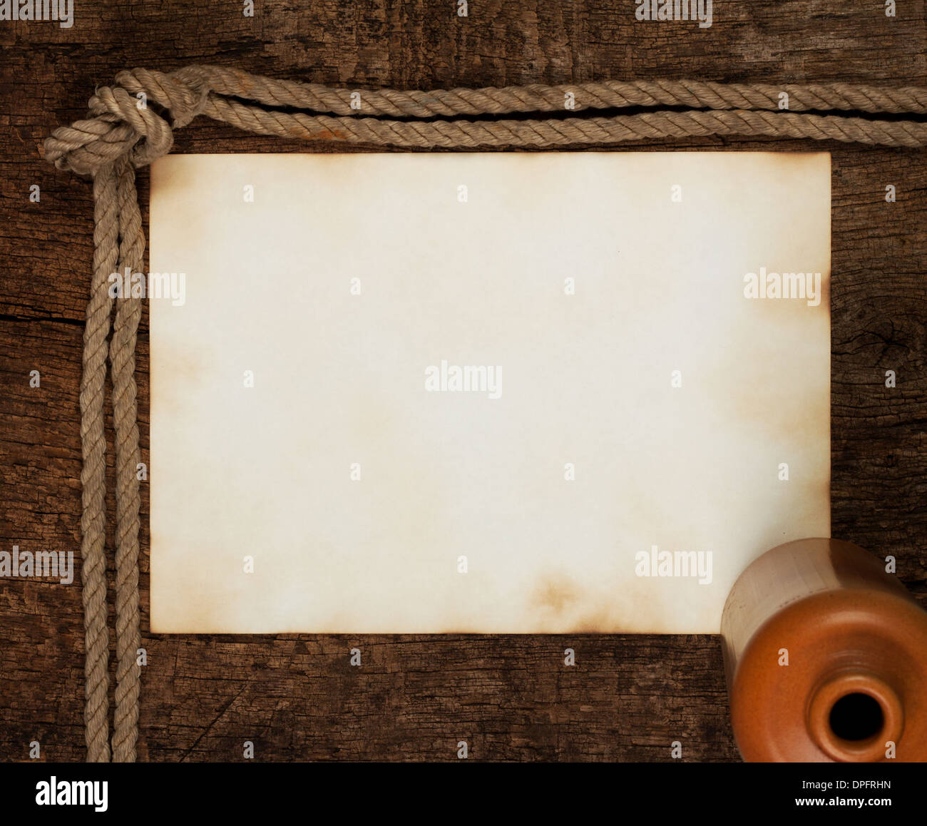 Sheet of old paper with a bottle on a wooden background - Stock Image