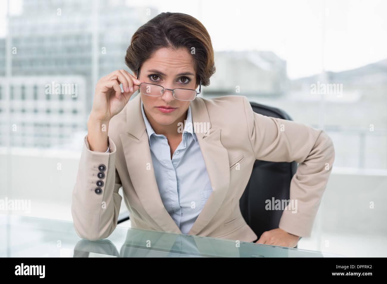 Dubious businesswoman looking at camera - Stock Image