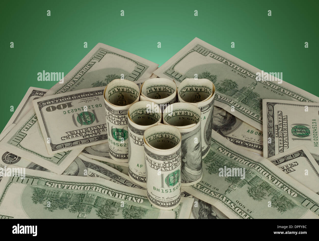 Triangle of hundred dollar bills on green background - Stock Image
