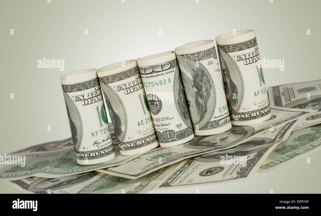 Twisted hundred dollar bill on the carpet of notes on a green background - Stock Image