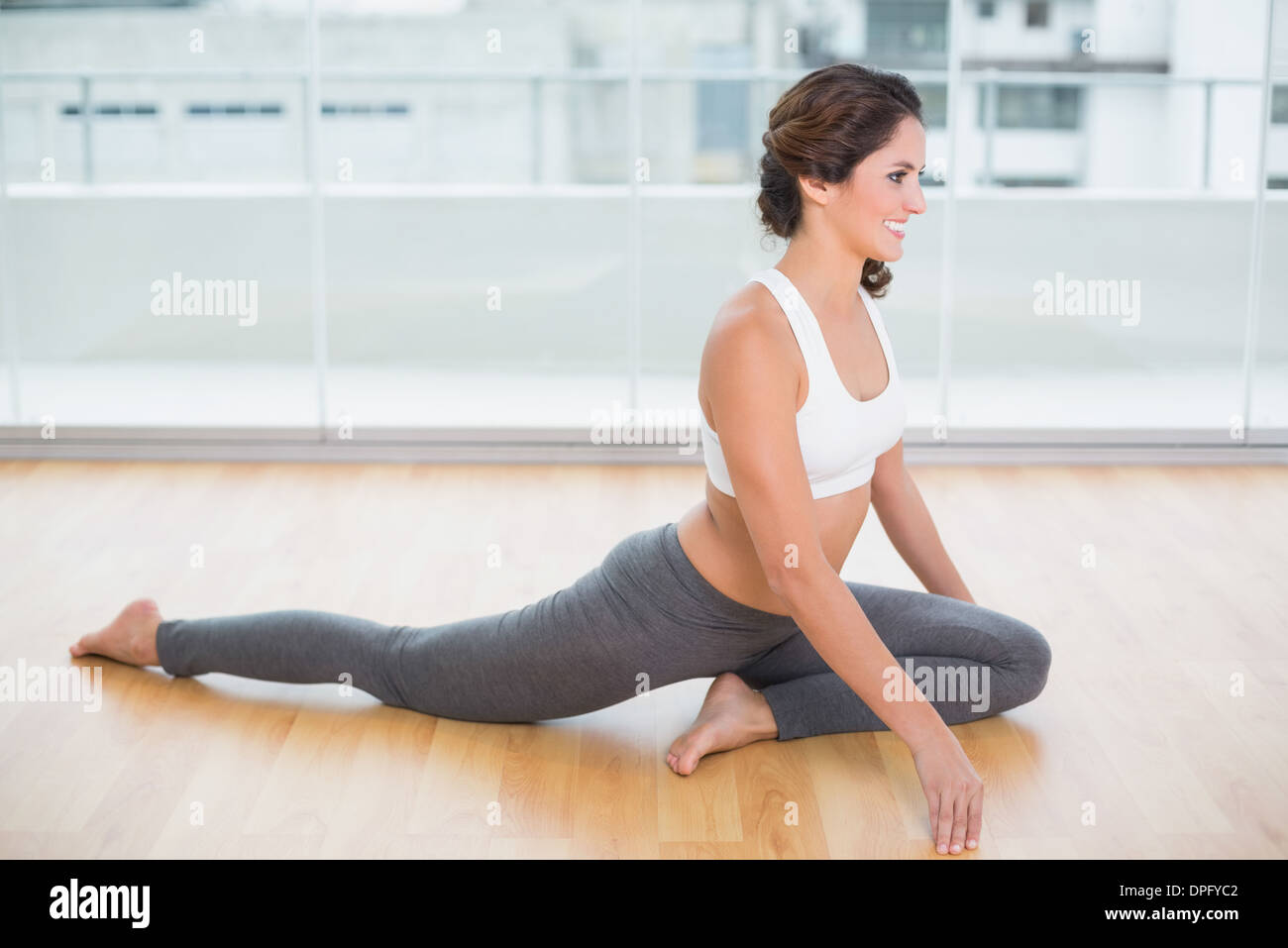 Sporty gleeful brunette stretching on the floor - Stock Image
