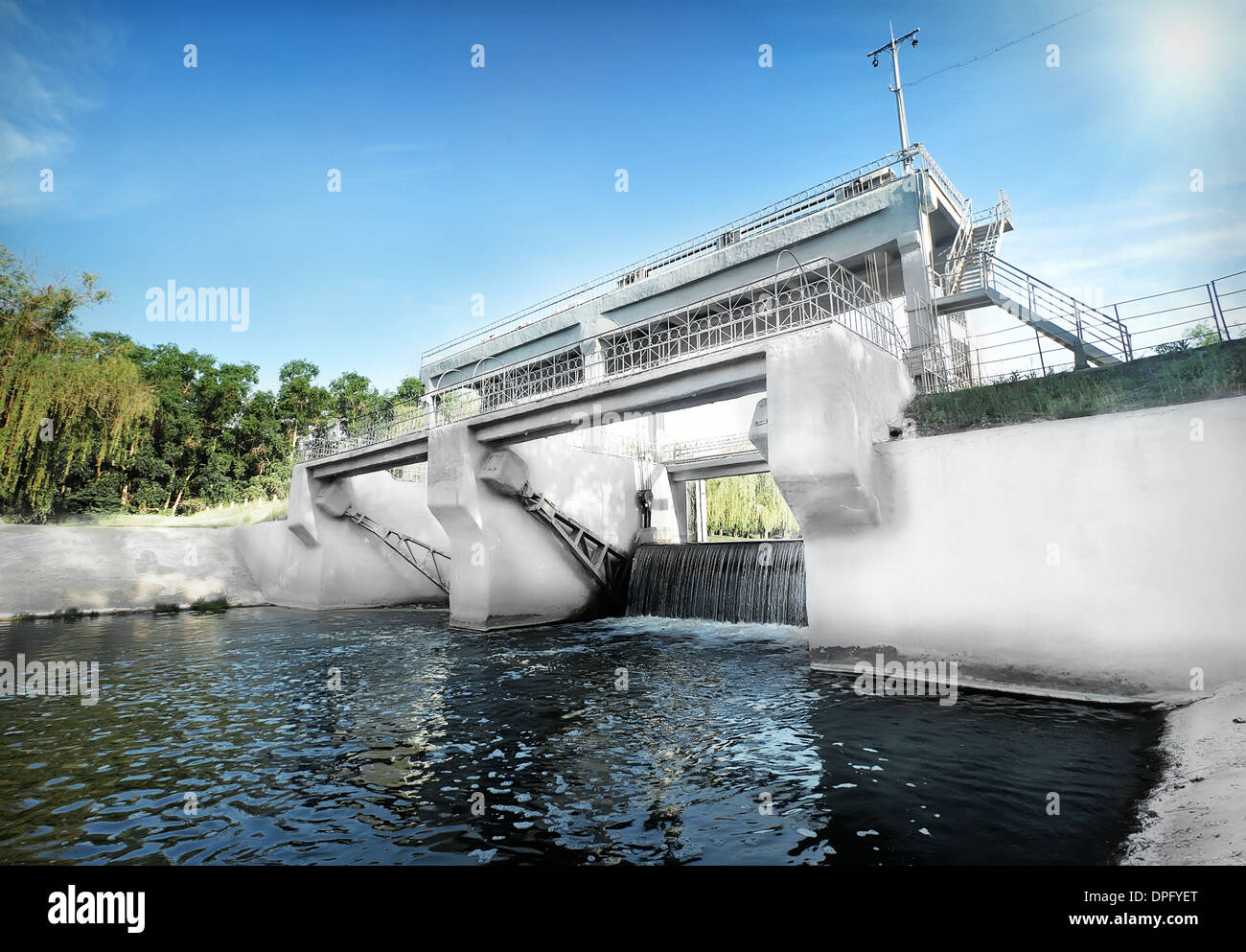 White stone dam on the river under the sky - Stock Image