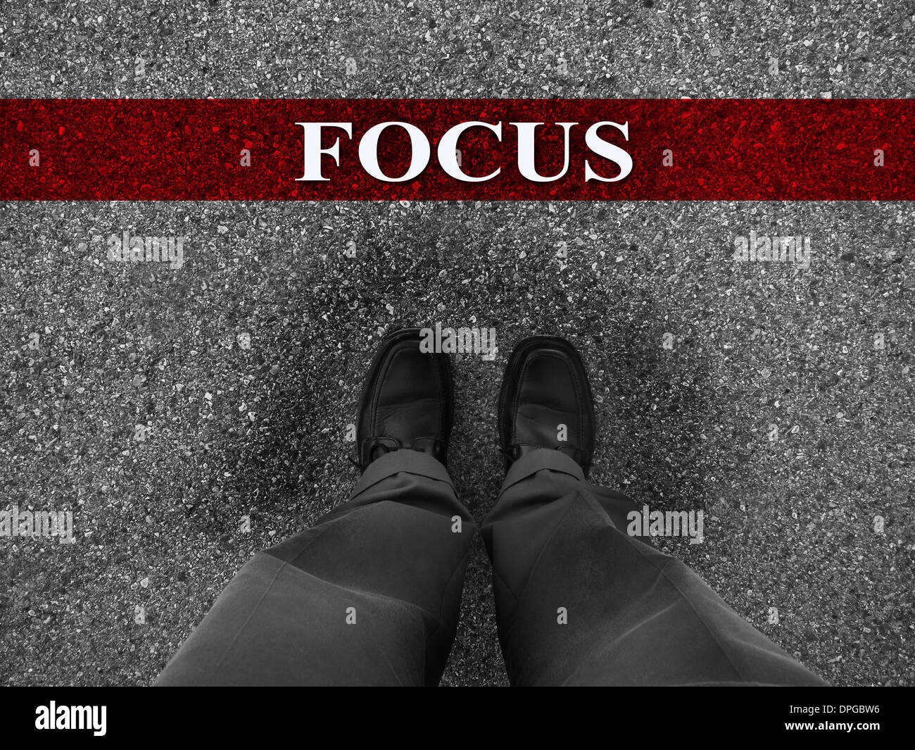 Businessman standing on asphalt starting line with motivation word of Focus Stock Photo